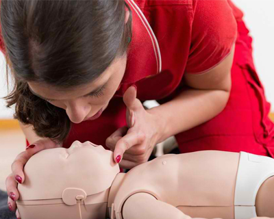 a medical student doing CPR to a dummy baby