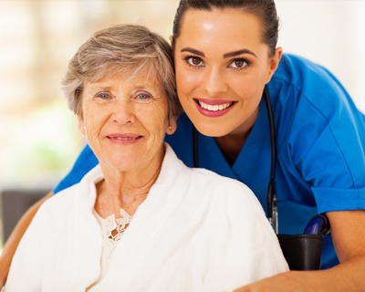 a caregiver and a senior woman in wheelchair smiling