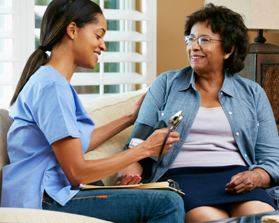 a caregiver checking the blood pressure of a senior woman