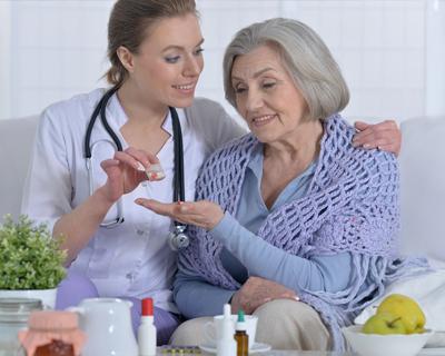 a nurse giving medicine to a senior woman