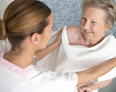a caregiver helping a senior woman take a shower